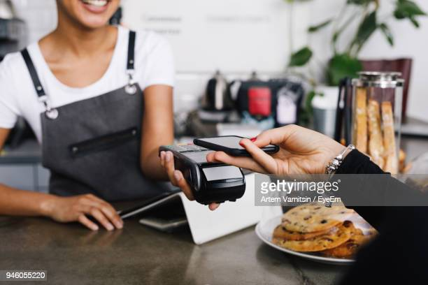cropped hand of customer using mobile phone for contactless payment to owner at cafe - pagando - fotografias e filmes do acervo