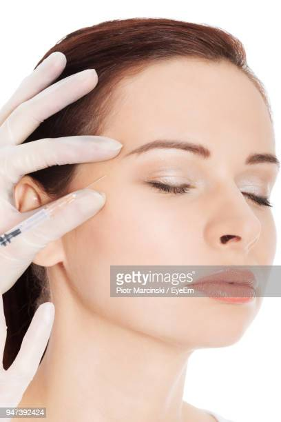 Cropped Hand Of Doctor Giving Botox Injection To Woman On White Background