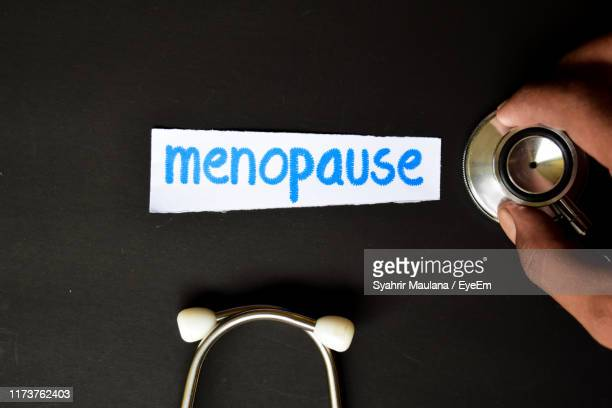 cropped hand of doctor holding stethoscope by text on paper over black background - menopause stock pictures, royalty-free photos & images