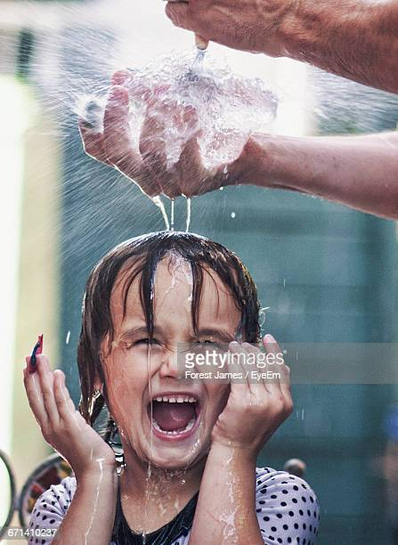 Cropped Hand Of Father Bursting Water Bomb Over Happy Daughter Head