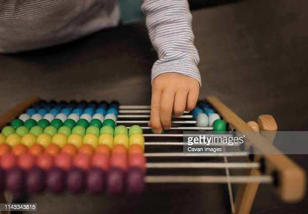 cropped hand of girl using abacus on table at home - bead stock pictures, royalty-free photos & images
