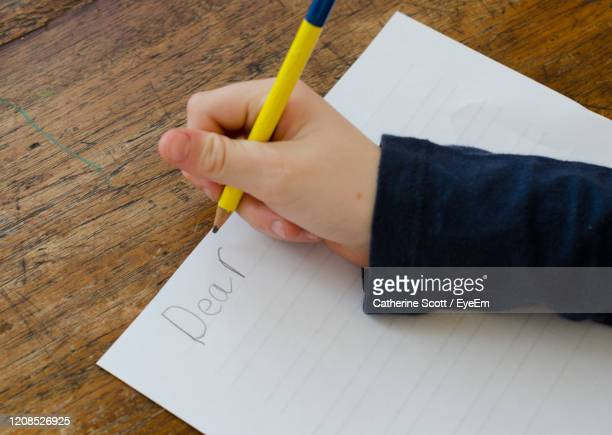 cropped hand of girl writing in paper on table - handwriting stock pictures, royalty-free photos & images