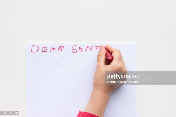 cropped hand of girl writing on paper over white background - crayon stock pictures, royalty-free photos & images