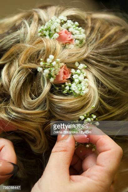 Cropped Hand Of Hairdresser Adjusting Flowers In Hair