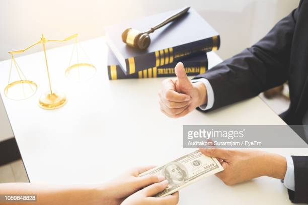cropped hand of lawyer gesturing thumbs up while receiving fee from client in courtroom - fee stock pictures, royalty-free photos & images