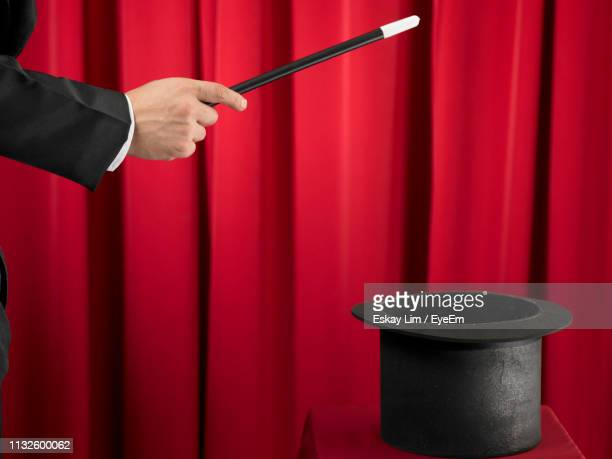 cropped hand of magician holding magic wand over hat - 手品師の杖 ストックフォトと画像