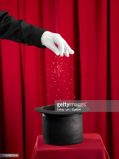 cropped hand of magician sprinkling sparkles in hat by curtains - goochelaar stockfoto's en -beelden