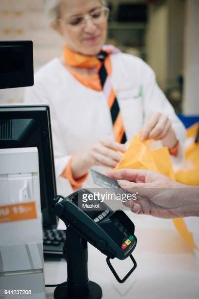 Cropped hand of male customer using contactless payment through credit card against pharmacist at checkout in store