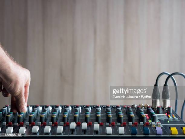 cropped hand of male dj playing music on sound mixer against wall - equaliser stock pictures, royalty-free photos & images