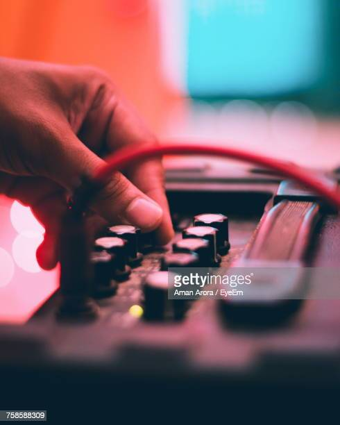 Cropped Hand Of Male Musician Using Amplifier In Recording Studio