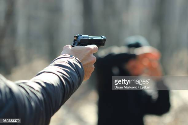 cropped hand of man aiming with gun at person - shooting crime stock pictures, royalty-free photos & images