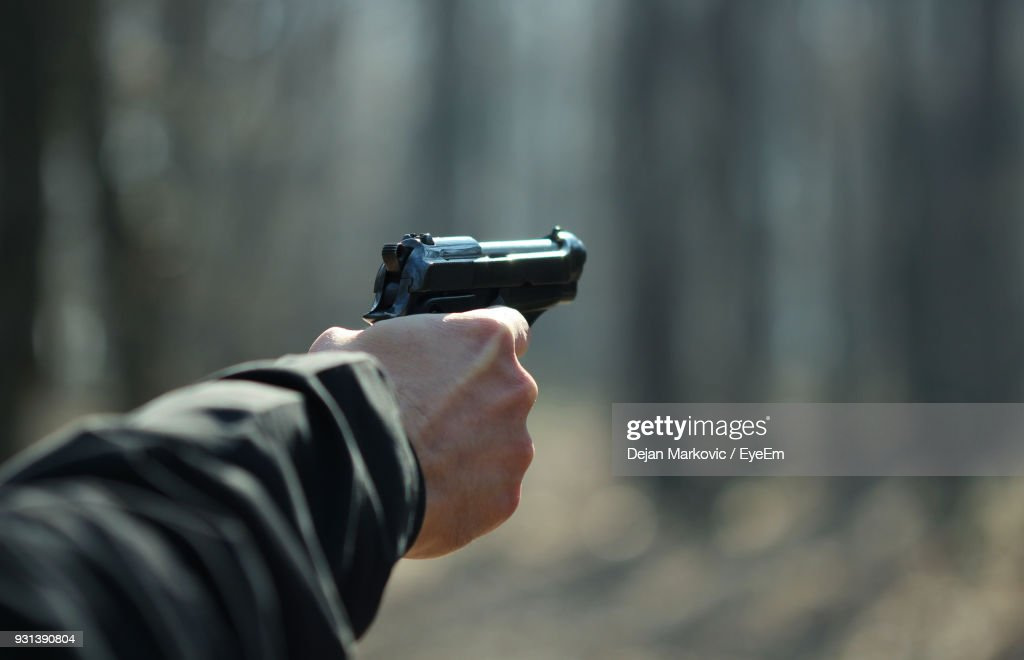 Cropped Hand Of Man Aiming With Gun : Stock Photo