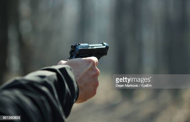 cropped hand of man aiming with gun - killing stock pictures, royalty-free photos & images