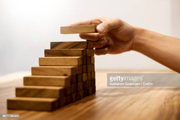 Cropped Hand Of Man Arranging Toy Blocks On Wooden Table