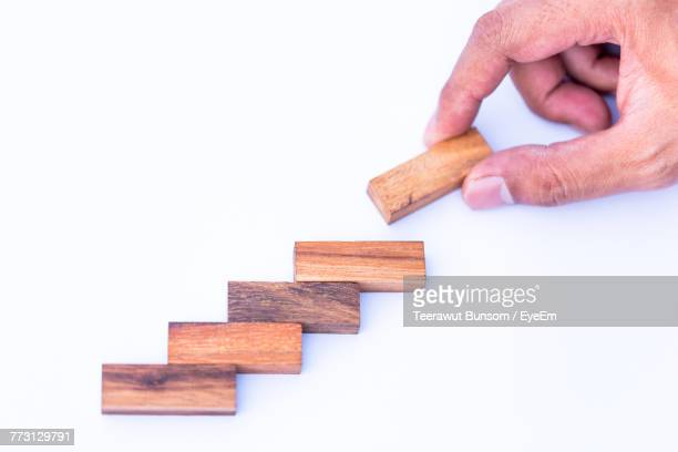 Cropped Hand Of Man Arranging Toy Blocks Over White Background