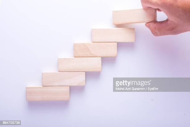 Cropped Hand Of Man Arranging Wooden Toy Blocks On Purple Background