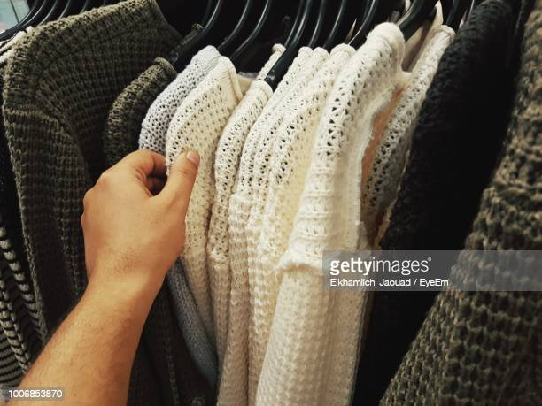 Cropped Hand Of Man Choosing Clothes From Rack