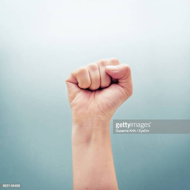 Cropped Hand Of Man Clenching Fist Against Blue Wall