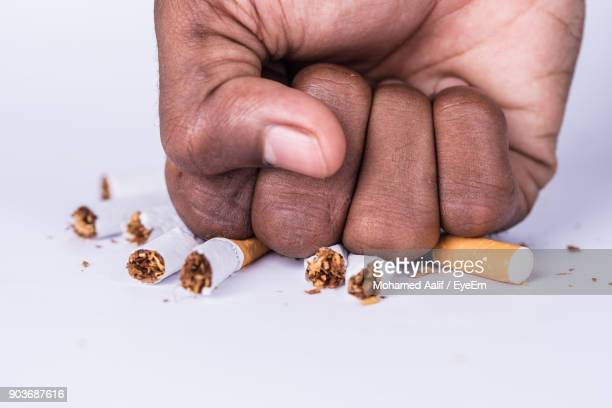 Cropped Hand Of Man Crushing Cigarette On White Background