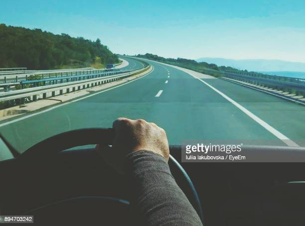 Cropped Hand Of Man Driving Car On Road Against Clear Sky