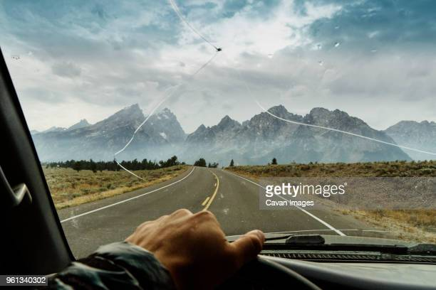 cropped hand of man driving truck - windshield stock pictures, royalty-free photos & images