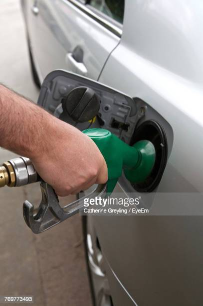 Cropped Hand Of Man Filling Fuel In Car