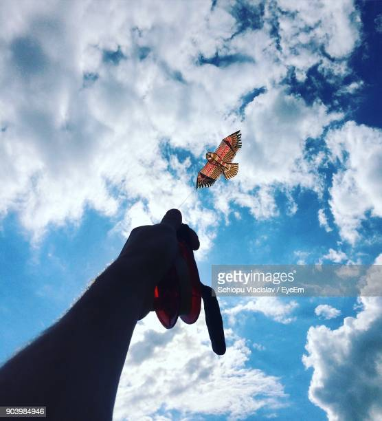 cropped hand of man flying kite against cloudy sky - kite toy stock pictures, royalty-free photos & images