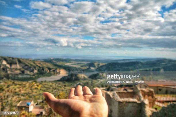 cropped hand of man gesturing against landscape - dito umano foto e immagini stock