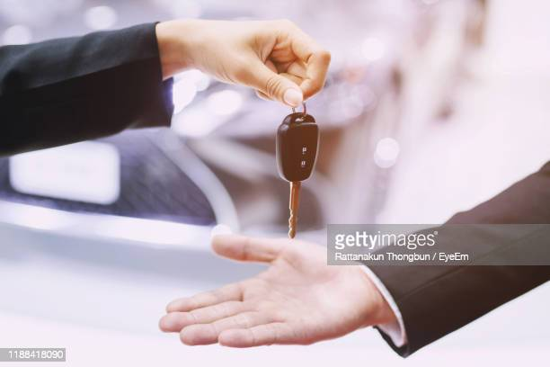 cropped hand of man giving key to person with car on road in background - receiving stock pictures, royalty-free photos & images