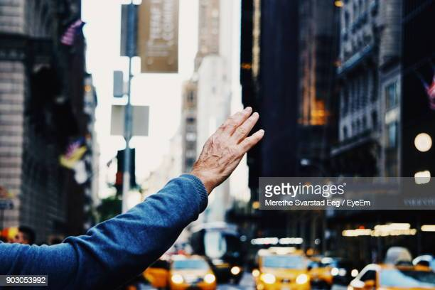 cropped hand of man hailing taxi in city - hail stock pictures, royalty-free photos & images