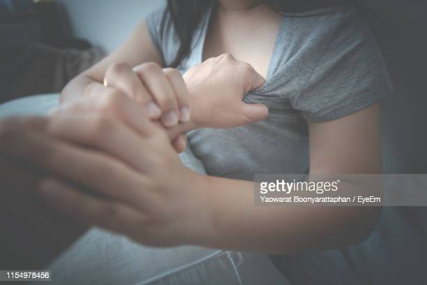 cropped hand of man harassing woman sitting on bed at home - violenza foto e immagini stock