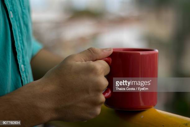 Cropped Hand Of Man Having Coffee On Railing