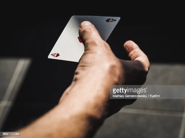 cropped hand of man holding ace on footpath - one man only stock pictures, royalty-free photos & images