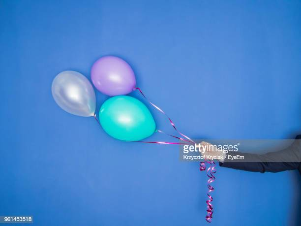 cropped hand of man holding balloon against blue background - multi colored suit stock photos and pictures