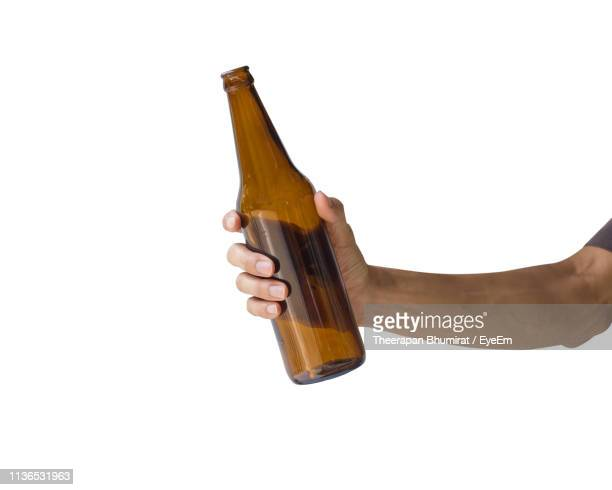 cropped hand of man holding beer bottle against white background - botella fotografías e imágenes de stock