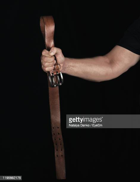 cropped hand of man holding belt against black background - belt stock pictures, royalty-free photos & images