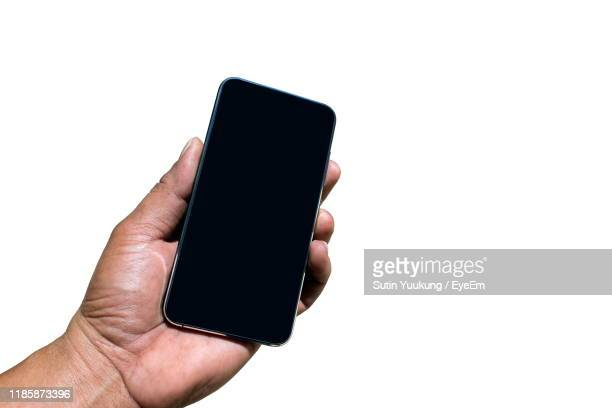 cropped hand of man holding blank mobile phone against white background - black hand holding phone stock pictures, royalty-free photos & images