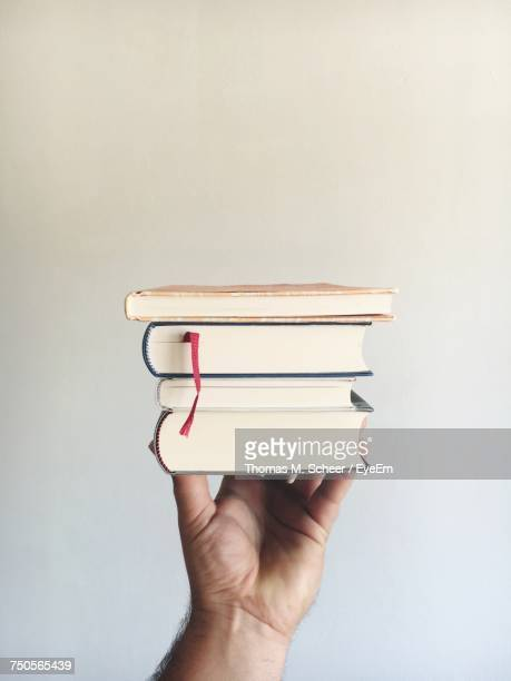 Cropped Hand Of Man Holding Books Against Gray Background