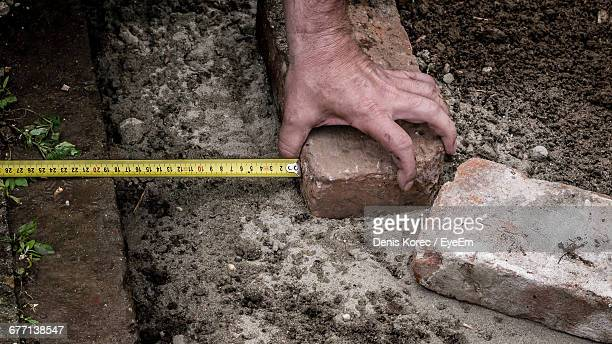 Cropped Hand Of Man Holding Brick By Tape Measure At Park