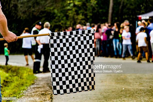 Cropped Hand Of Man Holding Checkered Flag Against People