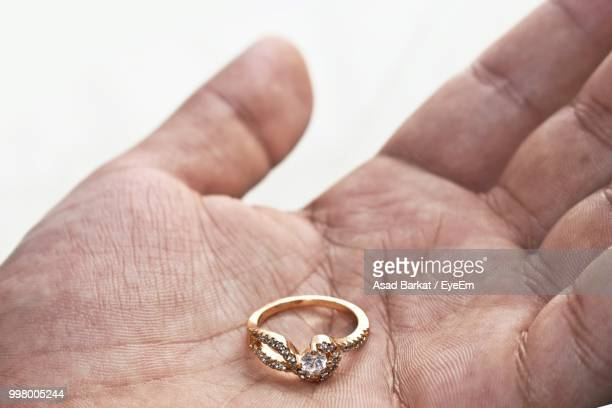 cropped hand of man holding diamond ring against white background - diamond ring stock pictures, royalty-free photos & images