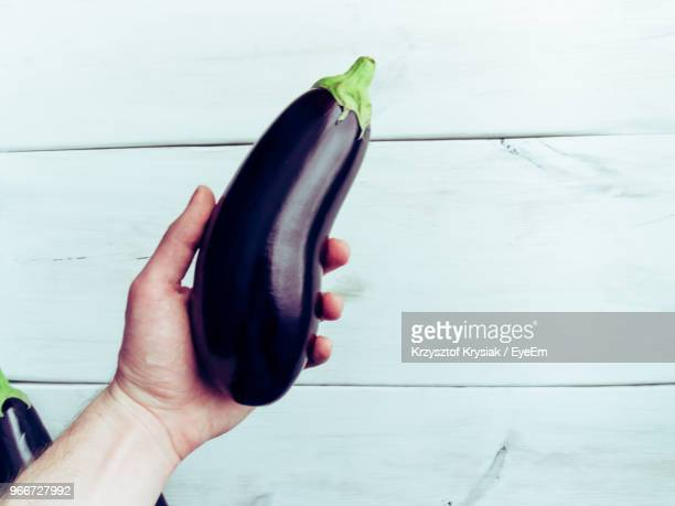 cropped hand of man holding eggplant over table - eggplant stock pictures, royalty-free photos & images