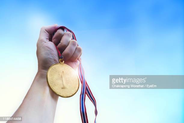 cropped hand of man holding gold medal against blue sky - gold medal stock pictures, royalty-free photos & images