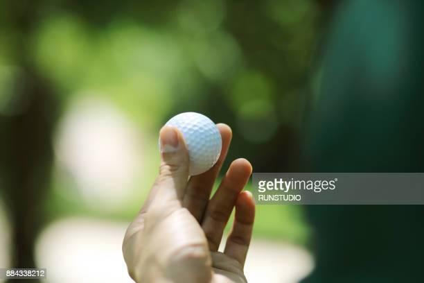cropped hand of man holding golf ball - ゴルフボール ストックフォトと画像