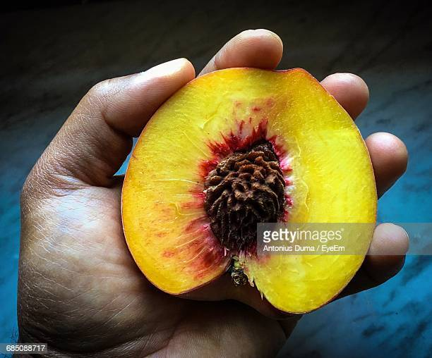 Cropped Hand Of Man Holding Halved Peach