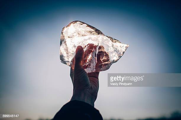 Cropped hand of man holding ice against sky at dusk