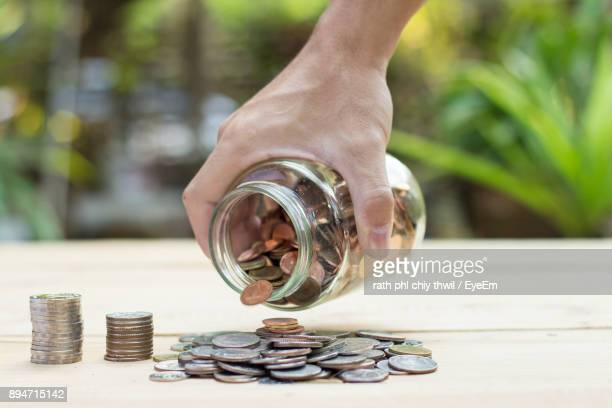Cropped Hand Of Man Holding Jar With Coins On Wooden Table