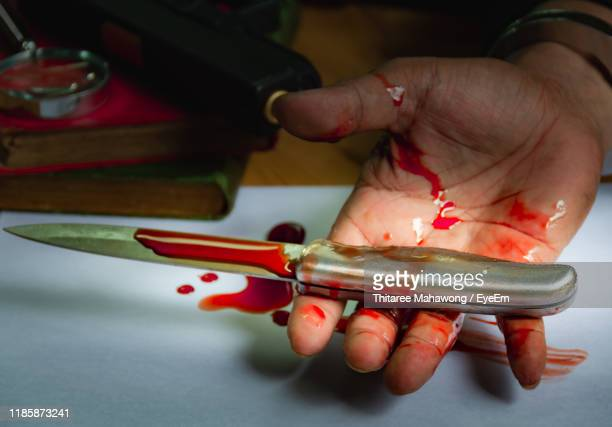 cropped hand of man holding knife with blood at sink - blood in sink stock pictures, royalty-free photos & images