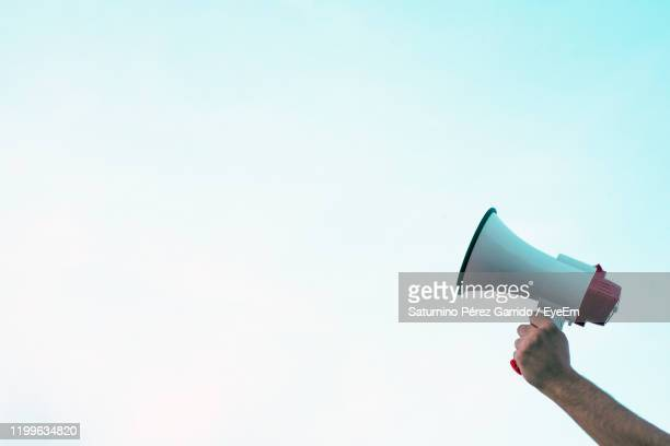cropped hand of man holding megaphone against clear sky - megaphone stock pictures, royalty-free photos & images