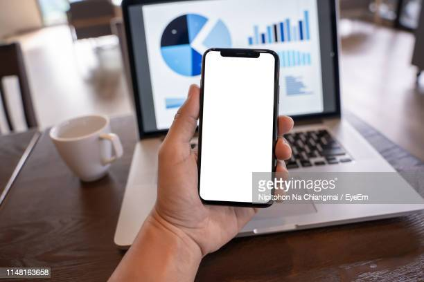 cropped hand of man holding mobile phone with blank screen at table - 可動性 ストックフォトと画像